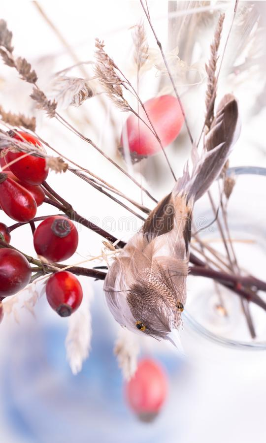 Autumn berries and artificial bird stock image