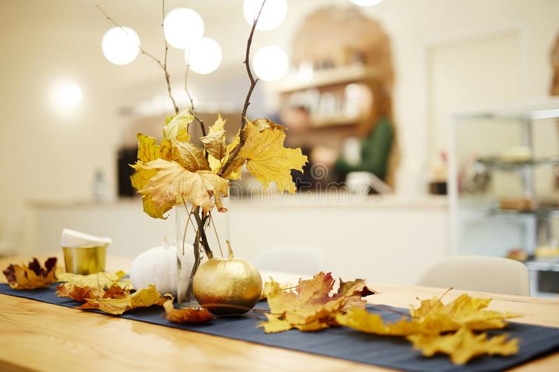 Autumn still life. Autumn bouquet in the vase standing on the table. And leaves decorating table royalty free stock photography