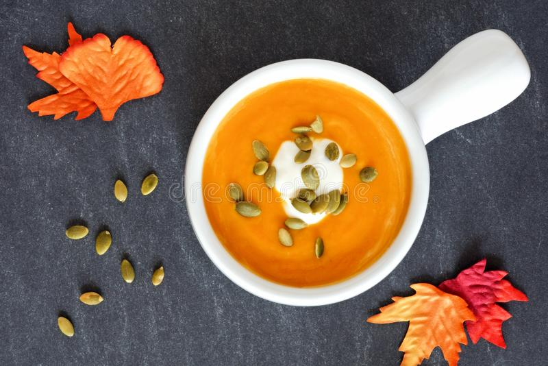 Autumn butternut squash soup on slate background. Creamy butternut squash soup topped with pumpkin seeds and cream on slate background with autumn leaves stock photography