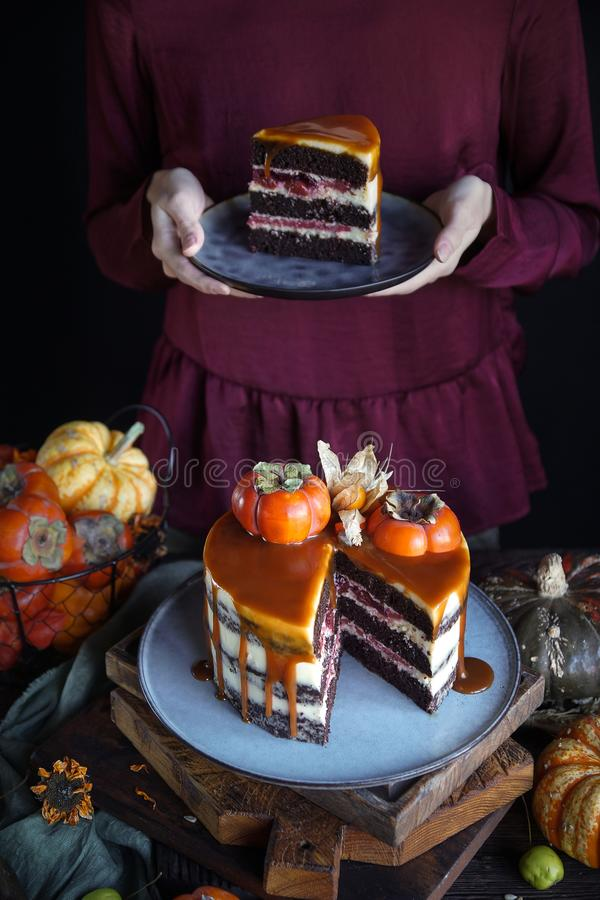 Autumn cake with persimmon and caramel with a pumpkin and a girl in a burgundy dress on a black background, Atmospheric dark food. Photos, Pastry Homemade stock image