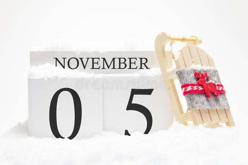 Autumn calendar made of wooden cubes with the date of November 5, the concept of the first snow and future holidays. Close-up stock image