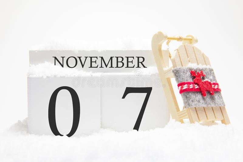Autumn calendar made of wooden cubes with the date of November 7, the concept of the first snow and future holidays. Close-up stock photography