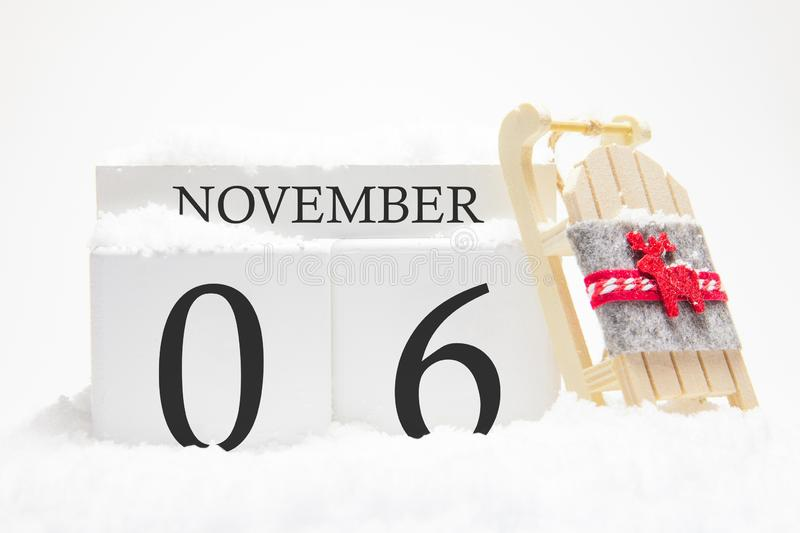 Autumn calendar made of wooden cubes with the date of November 6, the concept of the first snow and future holidays. Close-up stock images
