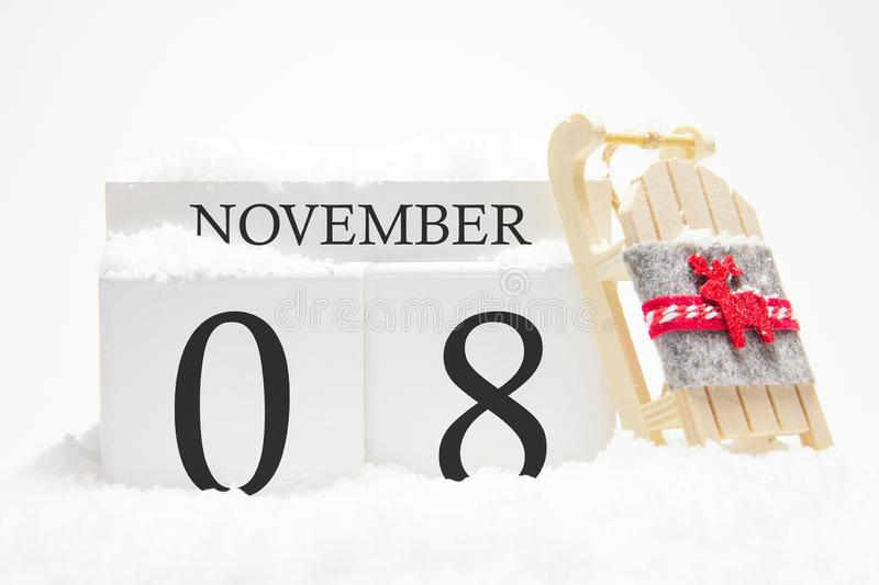 Autumn calendar made of wooden cubes with the date of November 8, the concept of the first snow and future holidays. Close-up royalty free stock photography
