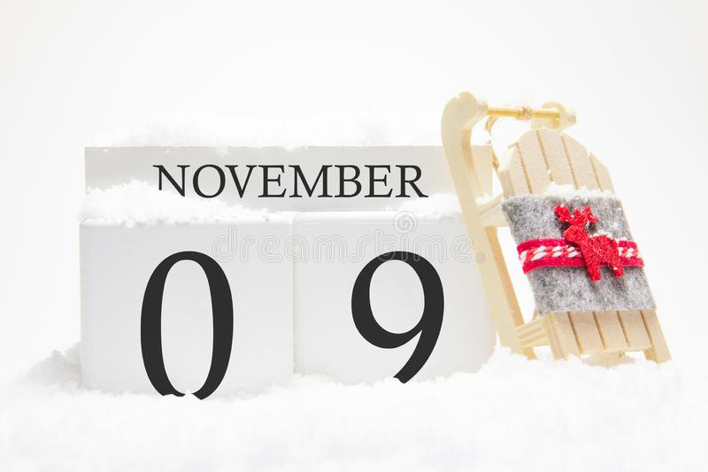 Autumn calendar made of wooden cubes with the date of November 9, the concept of the first snow and future holidays. Close-up royalty free stock photos