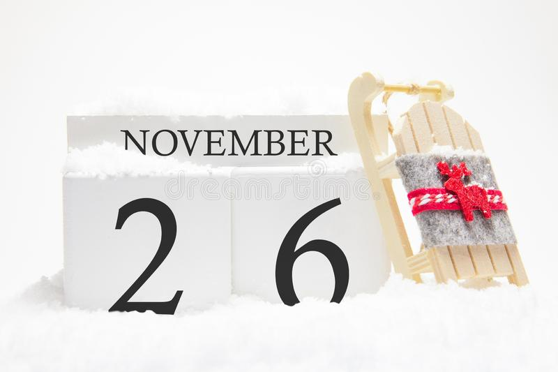 Autumn calendar made of wooden cubes with the date of November 26, the concept of the first snow and future holidays. Close-up stock image