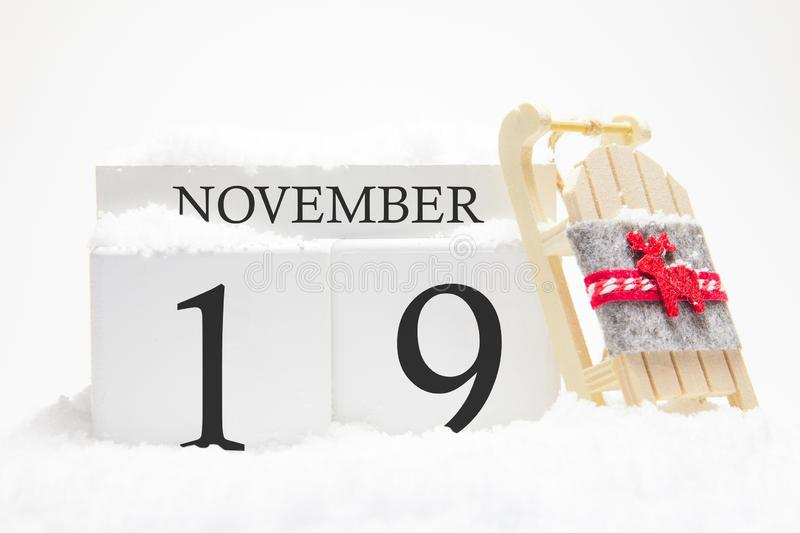 Autumn calendar made of wooden cubes with the date of November 19, the concept of the first snow and future holidays. Close-up stock photography