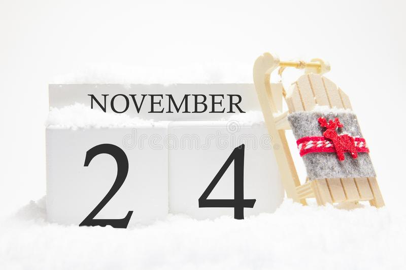 Autumn calendar made of wooden cubes with the date of November 24, the concept of the first snow and future holidays. Close-up stock photos