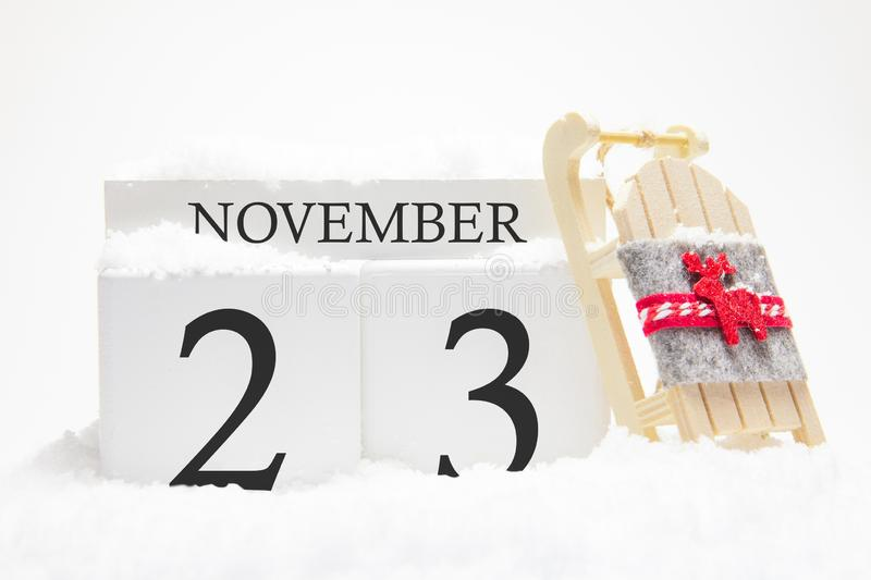 Autumn calendar made of wooden cubes with the date of November 23, the concept of the first snow and future holidays. Close-up stock images