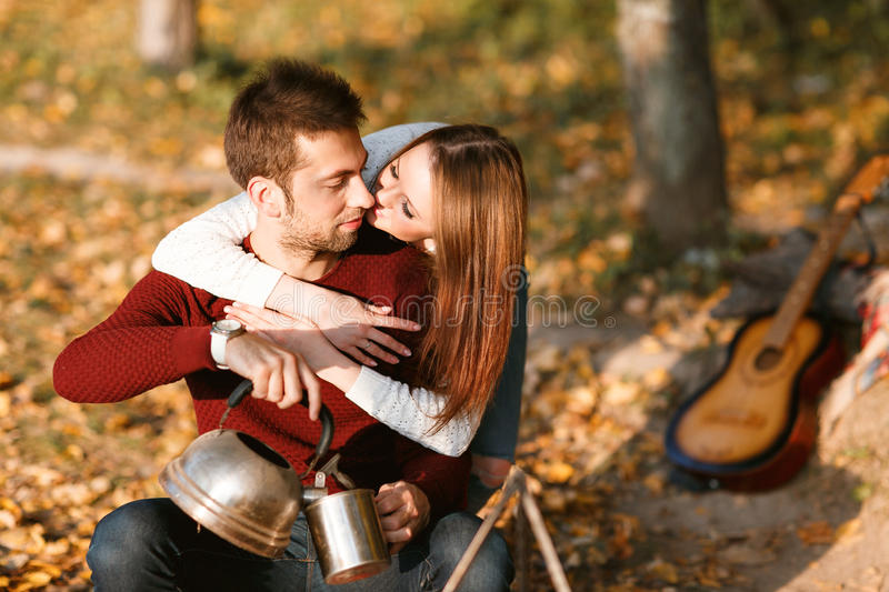Autumn camping. happy couple hugging and making tea or coffee. warm drinks. royalty free stock photography