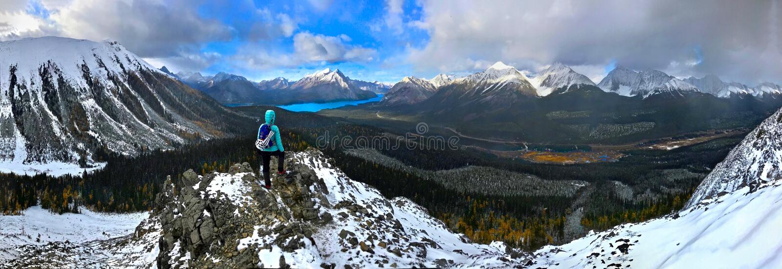 Woman on the mountain top looking at view of snow capped peaks and turquoise lake. royalty free stock image
