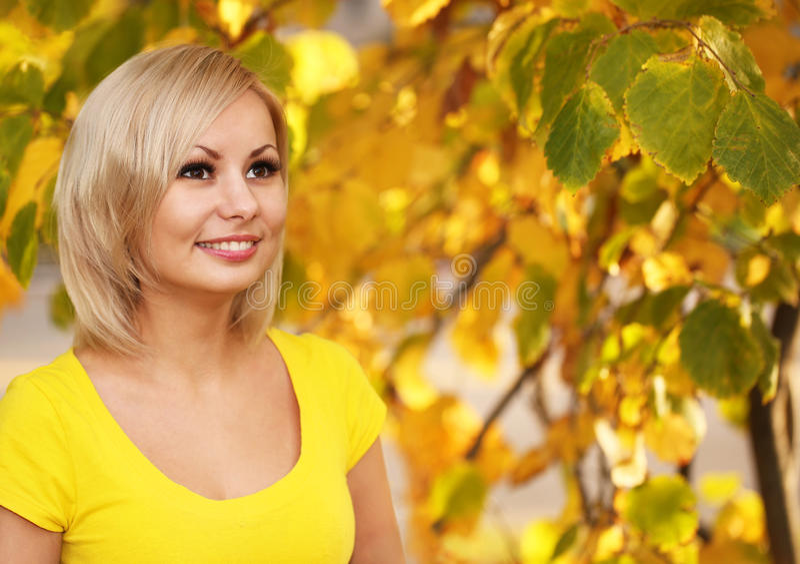 Autumn Cheerful Woman Blondemeisje en Gele Bladeren stock foto's