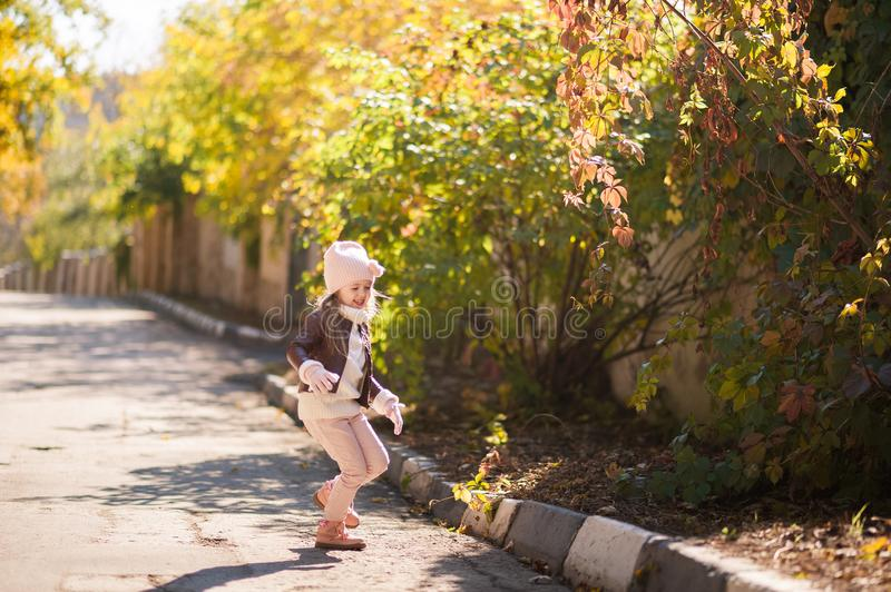 Autumn children`s fashion. A little girl dances, jumps and rejoices in the fall against a background of yellow and red foliage on stock images