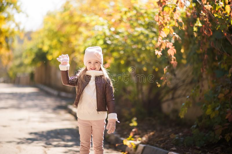 Autumn children`s fashion. A little girl dances, jumps and rejoices in the fall against a background of yellow and red foliage on stock photography