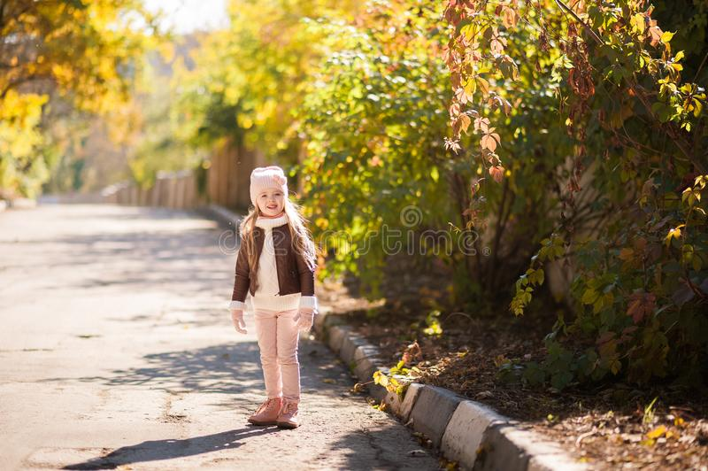 Autumn children`s fashion. A little girl dances, jumps and rejoices in the fall against a background of yellow and red foliage on stock photo