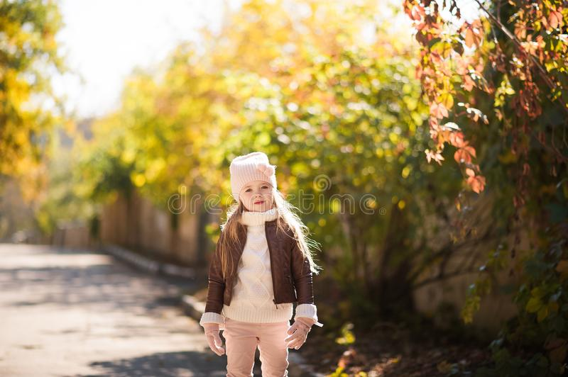 Autumn children`s fashion. A little girl dances, jumps and rejoices in the fall against a background of yellow and red foliage on royalty free stock image