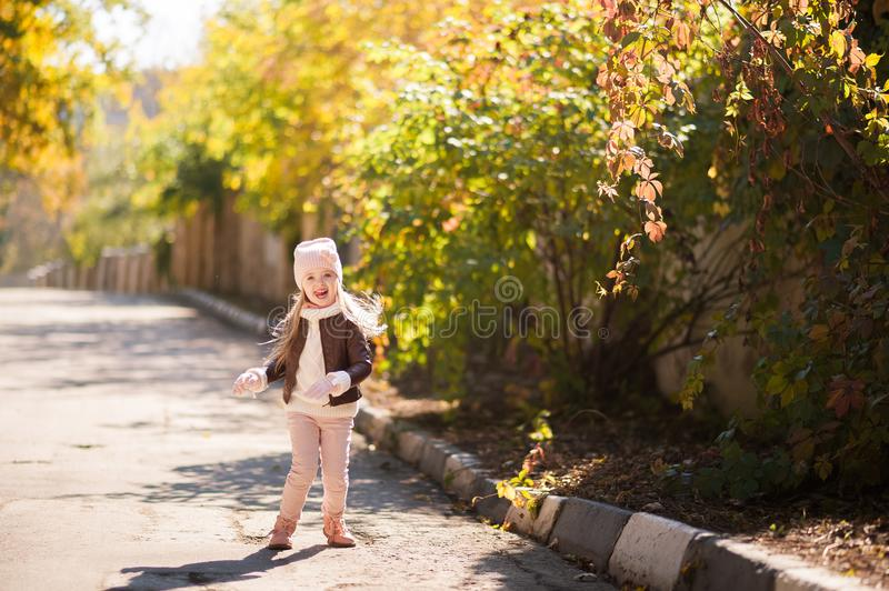 Autumn children`s fashion. A little girl dances, jumps and rejoices in the fall against a background of yellow and red foliage on stock photos