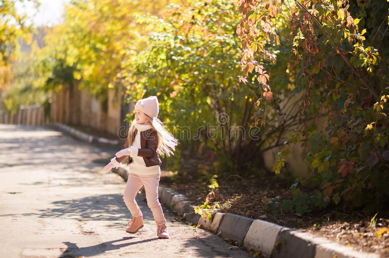 Autumn children`s fashion. A little girl dances, jumps and rejoices in the fall against a background of yellow and red foliage on royalty free stock photo