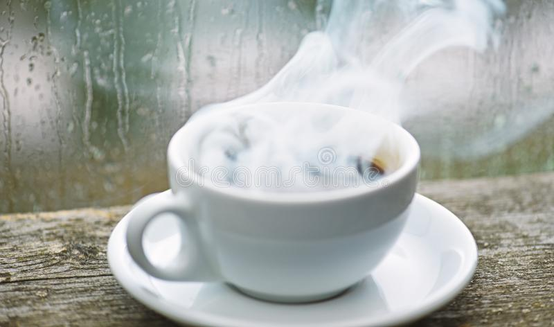 Autumn cloudy weather better with caffeine drink. Enjoying coffee on rainy day. Coffee time on rainy day. Fresh brewed. Coffee in white cup or mug on windowsill stock photos