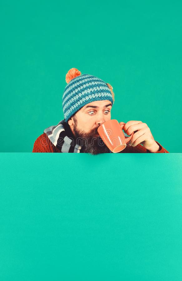 Autumn and cold weather concept. Hipster with beard. And shocked face drinks warm tea or coffee. Man in warm hat holds brown cup on green background, copy space stock images