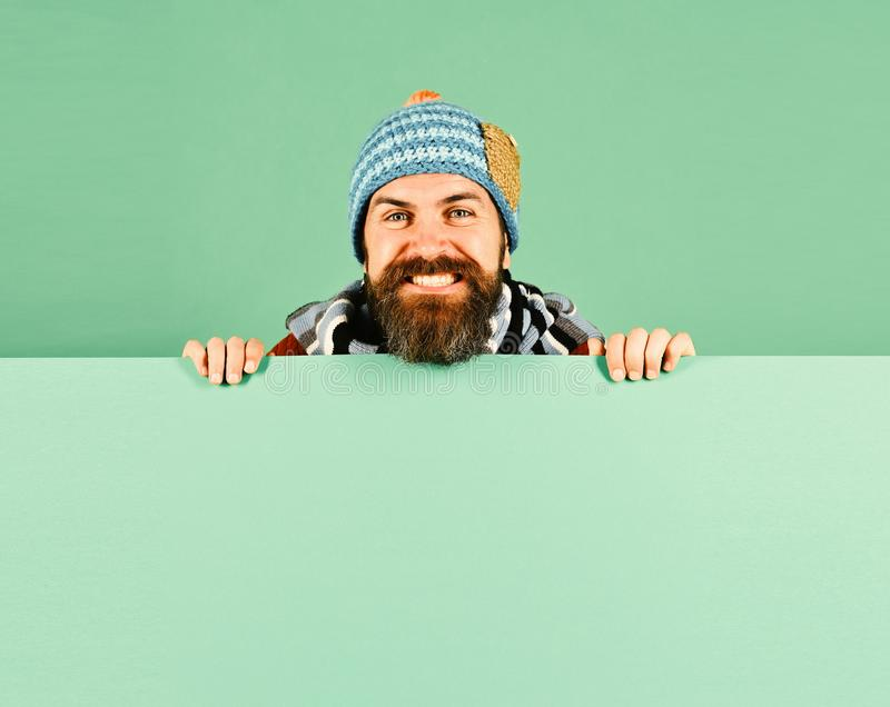 Autumn and cold weather concept. Hipster with beard and happy face wears warm clothes. October and November sale idea royalty free stock photos