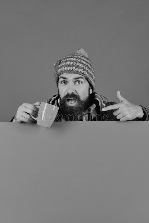 Autumn and cold weather concept. October and November beverage. Idea. Hipster with beard and questioning face points at tea or coffee. Man in warm hat holds royalty free stock photo