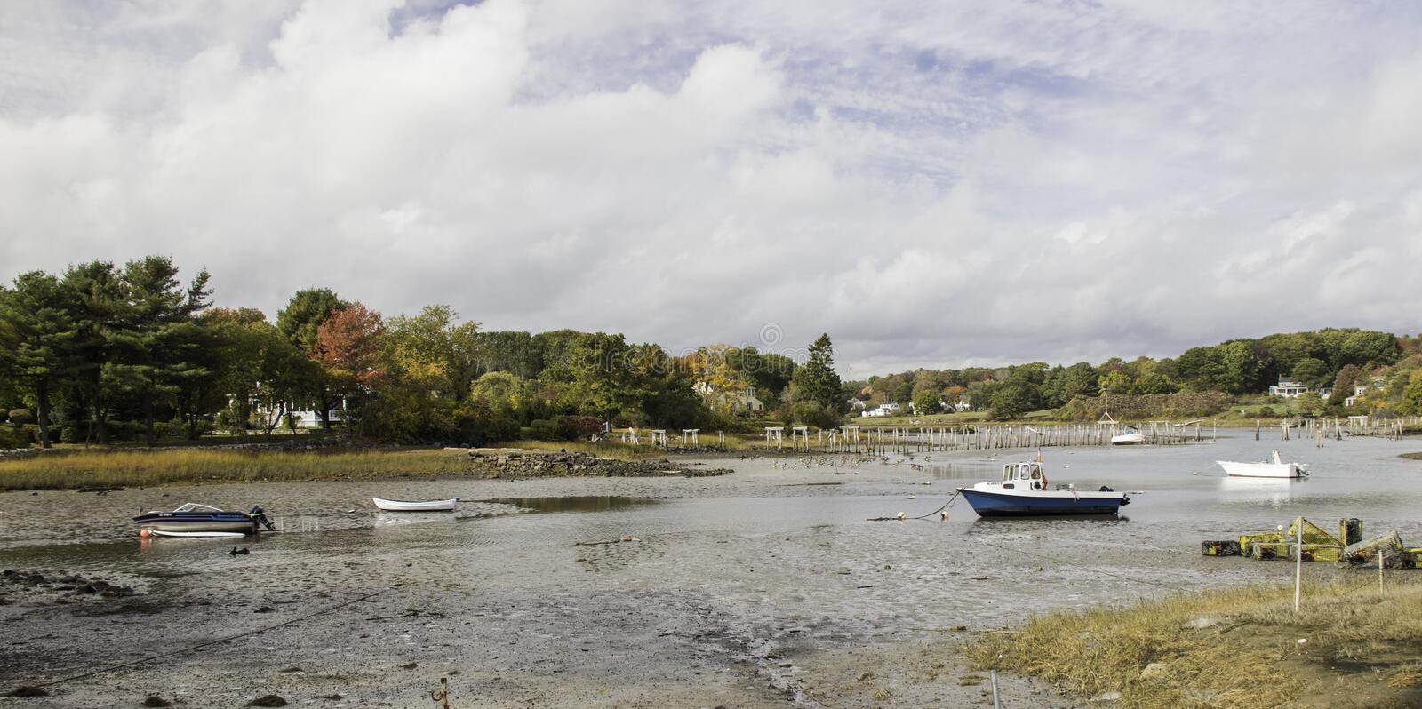 Autumn color and low tide with fishing boats aground royalty free stock photos