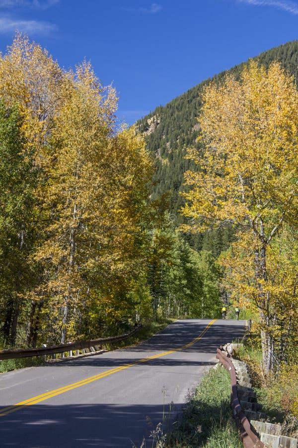 Autumn Colorado Rockies Highway Bikers. Autumn scene in the Colorado Rockies with highway and two bikers royalty free stock photo