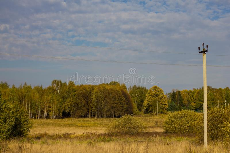 Autumn colorful landscape with views of the Russian field and forest. Electric pole on the background of yellow and orange trees stock photography