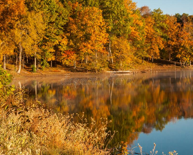 Autumn colors reflect off the lake stock image