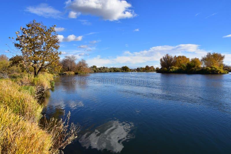 Autumn Colors und Wolke-gestreuter Himmel und Wasser, Yakima River Delta, nahe Richland, WA stockfotografie