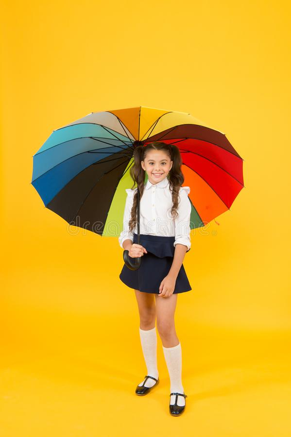 Autumn comes with weather changes. Small child holding colorful umbrella for autumn rain on yellow background. Little. Kid going to school on autumn day or royalty free stock photos