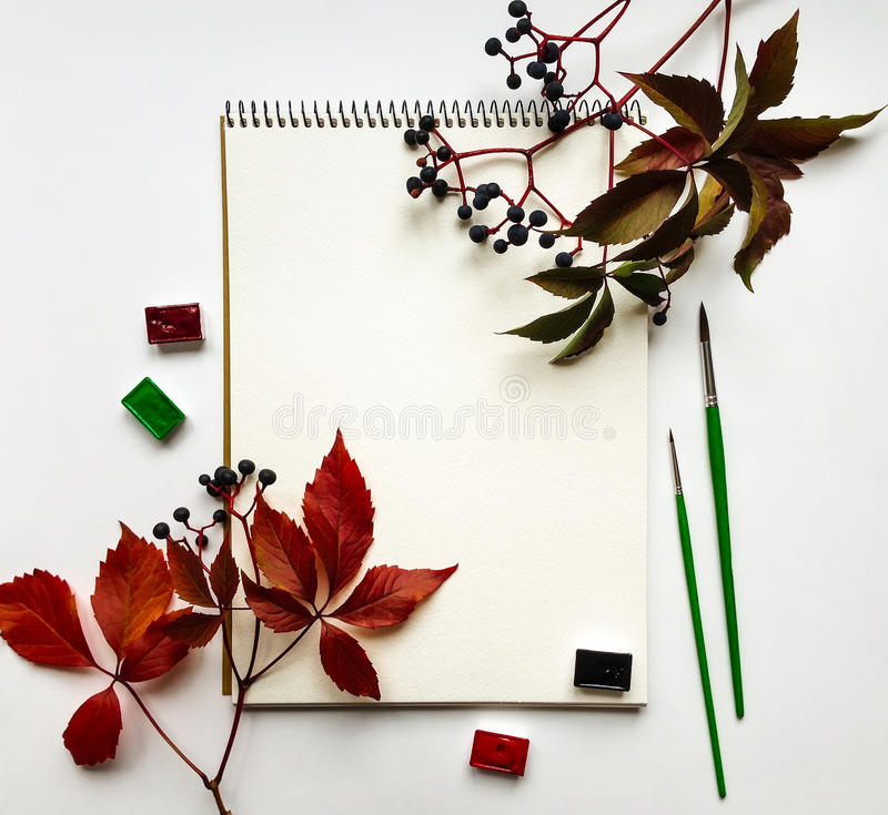 Autumn composition with album, watercolors and brushes, decorated with red leaves and berries. Flat lay, top view stock photo