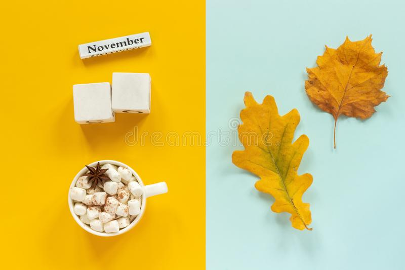 Autumn composition. Blank wooden white cubes mockup and November for your calendar data, cup of cocoa with marshmallows and yellow stock photo