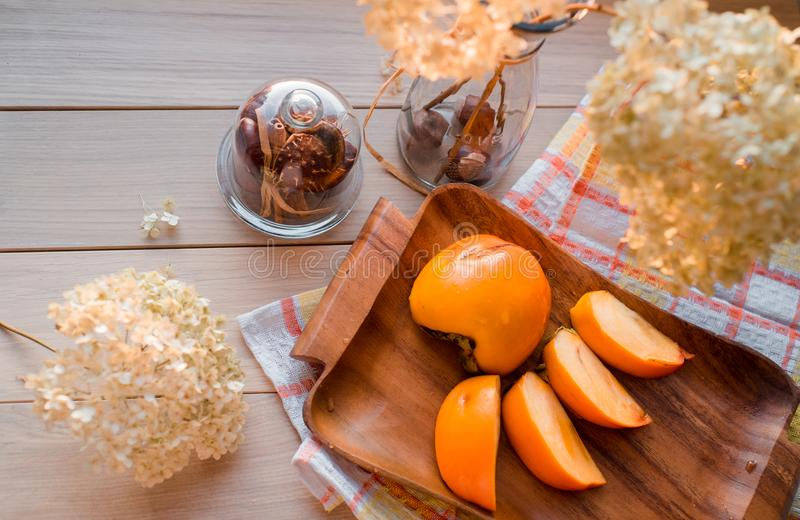 Autumn composition. Dried hydrangea, persimmon on a wooden tray on a yellow linen napkin royalty free stock image