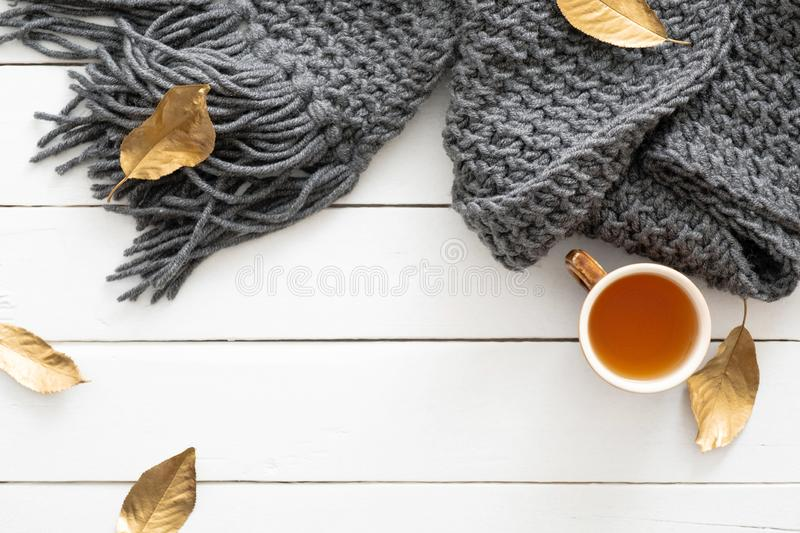 Autumn composition. Feminine desk table with knitted scarf, tea cup, fall leaves on wooden white background. Flat lay, top view. royalty free stock photos