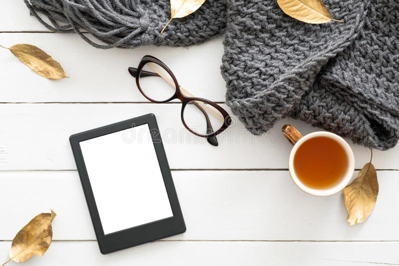 Autumn composition. Feminine desk table with knitted scarf, tea cup, glasses, tablet ebook with blank screen, fall leaves on stock photo