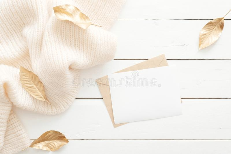 Autumn composition. Feminine desk table with letter, blank paper card, knitted scarf, fall leaves on wooden white background. Flat stock image