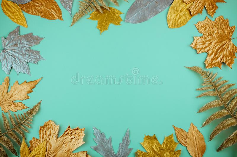 Autumn composition with golden leaves frame on blue mint background. Fall mockup with gold maple leaves. Flat lay, top view, copy royalty free stock photos