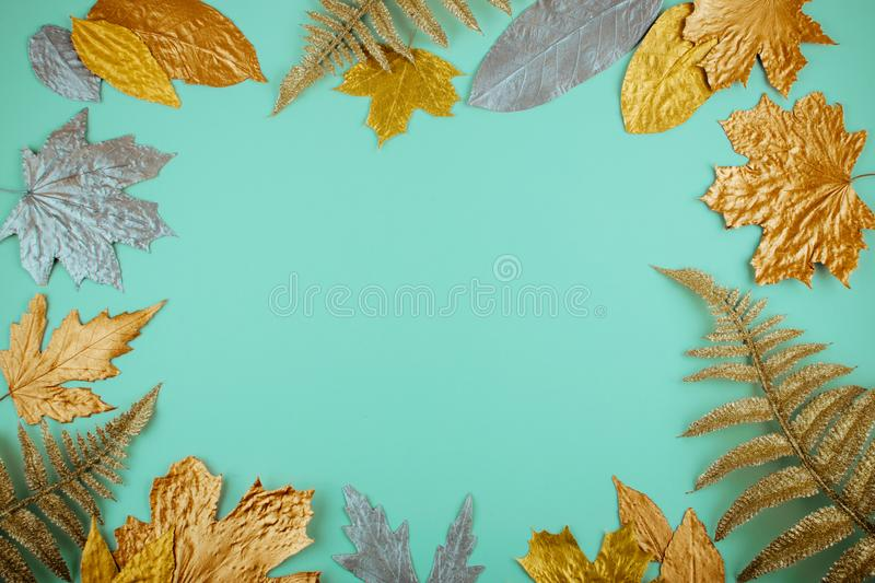Autumn composition with golden leaves frame on blue mint background. Fall mockup with gold maple leaves. Flat lay, top view, copy stock photos