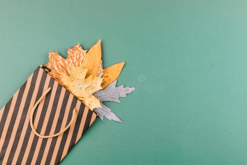 Autumn composition with golden leaves in gift bag on green paper background. Fall mockup with gold maple leaves. Flat lay, top royalty free stock image