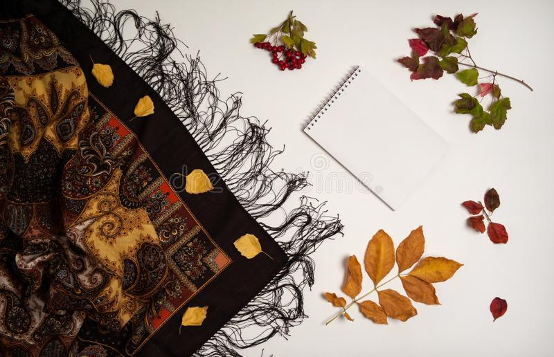 Autumn leaves of maple and birch, hawthorn berries, a large handkerchief, notepad on a white background. stock photography