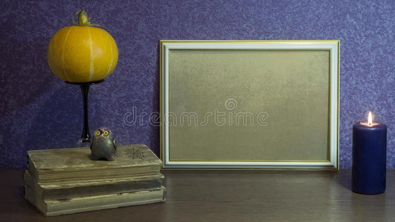 Autumn composition. A photoframe, books, a pumpkin and a candle on a beautiful background. Autumn, Halloween concept. royalty free stock photo