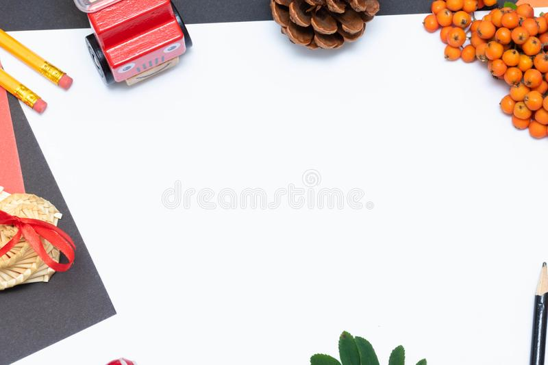 Autumn composition. White sheet of copyspace paper, bell, pencil, supplies, mountain ash, toy. Nobody. Back to school royalty free stock image