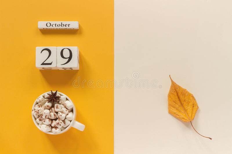 Autumn composition. Wooden calendar October 29, cup of cocoa with marshmallows and yellow autumn leaves on yellow beige background. Top view Flat lay Mockup stock photo