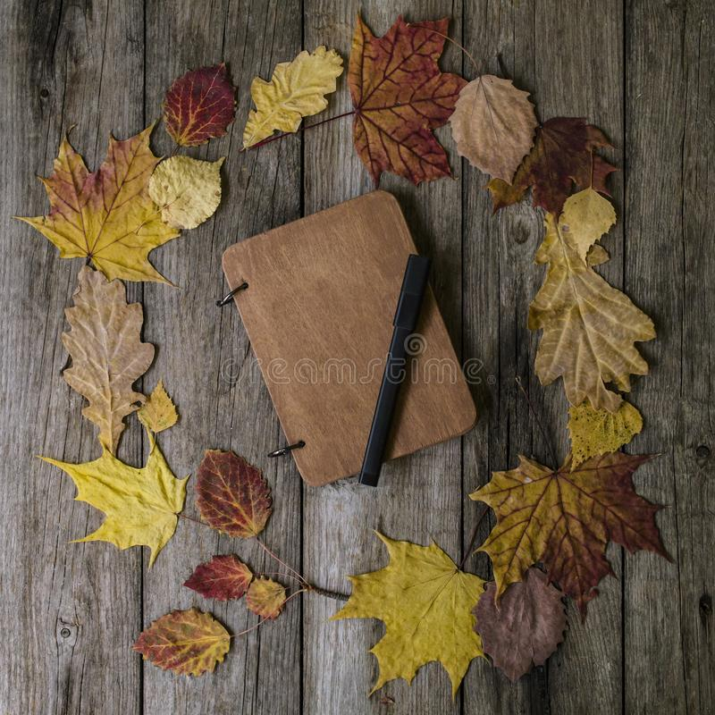 Autumn composition with workspace with blank notebook, pencil and beautiful colored dry leaves. Top view, flat lay stock photography