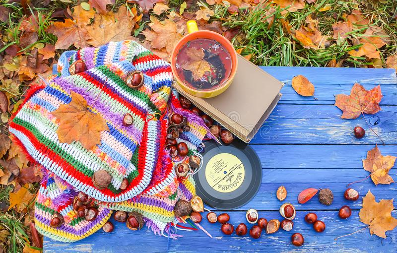Autumn composition of yellow ceramic cup of herbal tea and vintage vinyl records on aged wooden background with bright handmade. Crocheted plaid, old book, fall royalty free stock photo