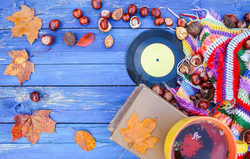 Autumn composition of yellow ceramic cup of herbal tea and vintage vinyl records on aged wooden background with bright handmade. Crocheted plaid, old book, fall royalty free stock images