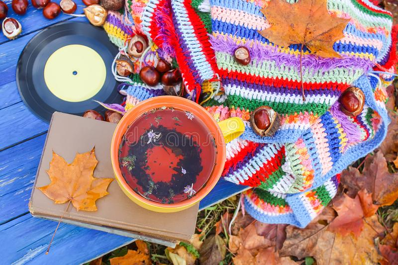 Autumn composition of yellow ceramic cup of herbal tea and vintage vinyl records on aged wooden background with bright handmade. Crocheted plaid, old book, fall royalty free stock photography