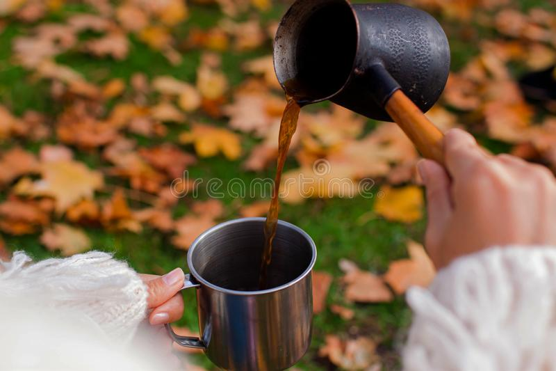 Autumn concept. Beautiful woman wearing white sweater with coffee mug sitting against fall nature background. stock image